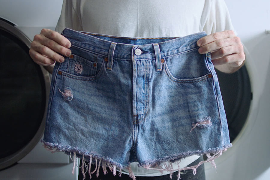 A person holds up a pair of Levi's shorts with a pink tint photo