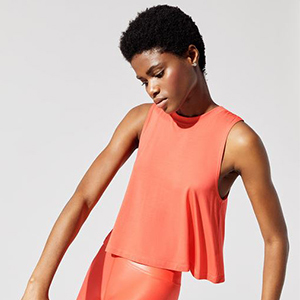 Woman wearing a coral crop top tank top and coral pants photo