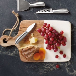 Wood and marble cheese board with cheese knives and a spread of grapes, cheese, and dried apricots. photo