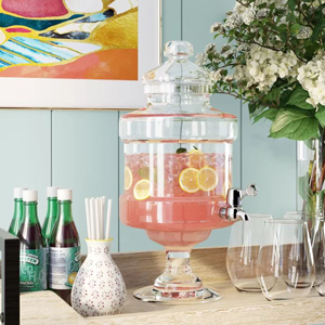 Clear beverage dispenser full of pink punch with lemons in it. photo