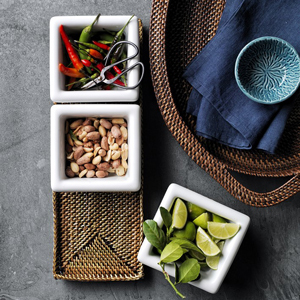 Condiment caddy with removable white ceramic bowls filled with nuts, limes, and peppers in a handwoven tray. photo