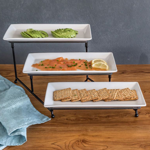 Three-tiered serving set with crackers, smoked salmon, and avocado. photo