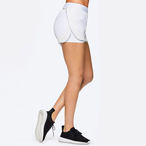 Woman wearing white running shorts and black tennis shoes photo