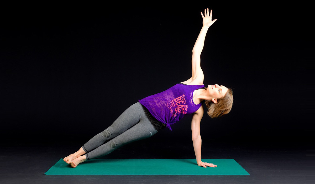 Woman holding side plank on a yoga mat wearing a purple tank and gray leggings.