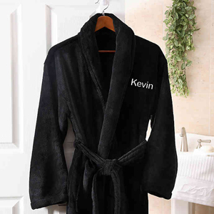 Men's black fleece robe with customized name on the chest from Bed Bath and Beyond hanging up in a bathroom photo