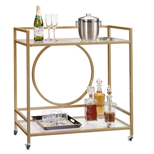 Gold bar cart with two levels and circle along the back, with bottles, glasses, and trays photo