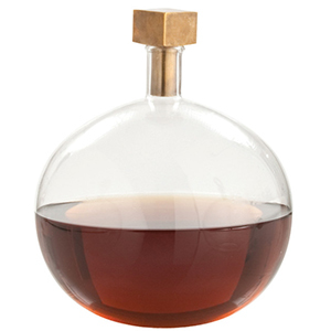 Clear glass decanter with gold square topper, filled with brown liquid photo