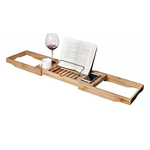 Light-wood bamboo bathtub caddy with wine, book, and phone photo