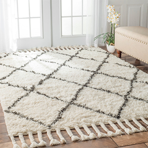 White rug with gray diamond detail and tassels photo