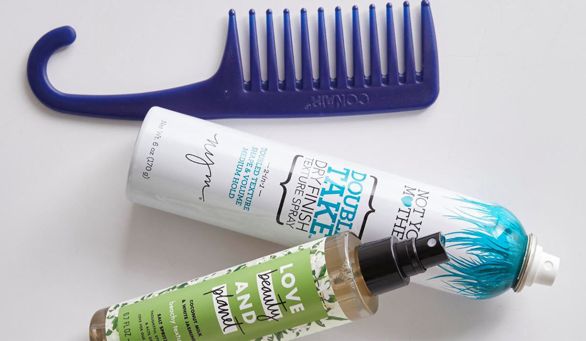 A shower comb and two hairstyling bottles photo
