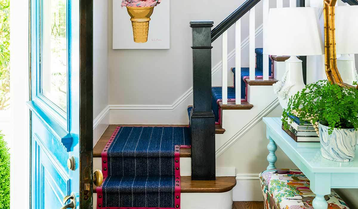 Entryway with wood flooring, a stairway, and a light blue table with books photo