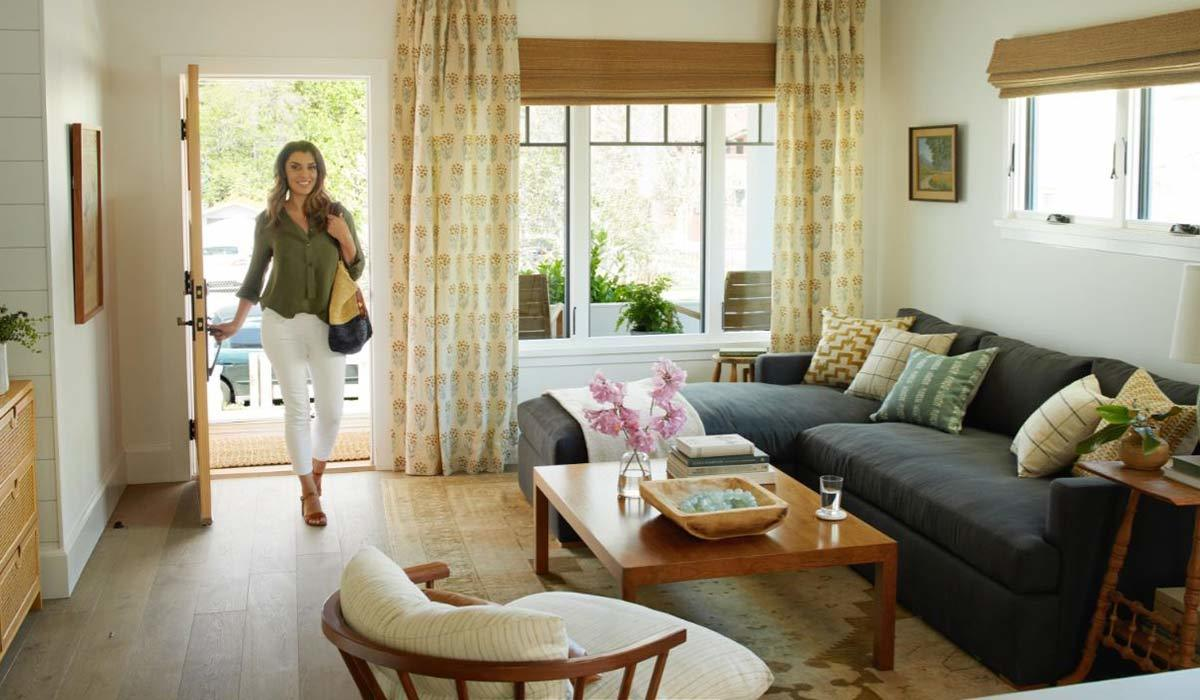 Woman walking into a living room with wooden floor and charcoal sectional photo