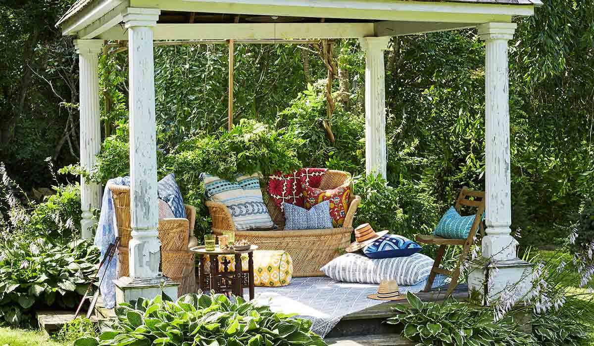 Gazebo with wicker furniture and blue and white pillows photo