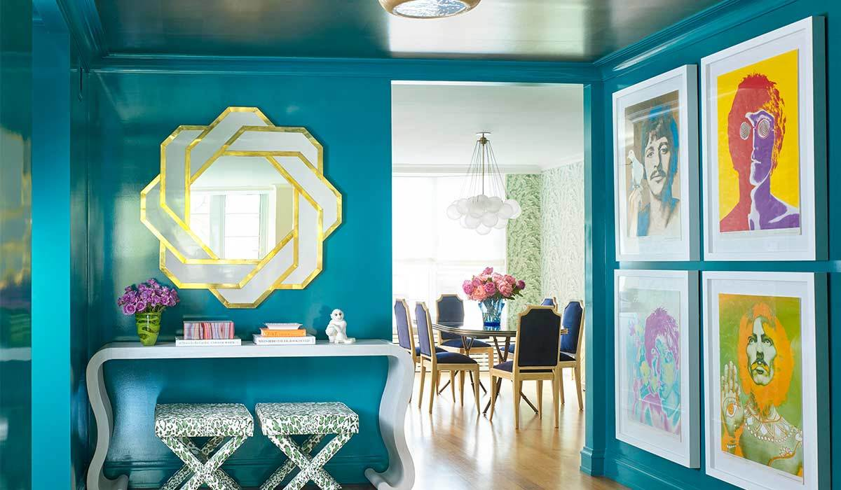 Blue room with a white desk and two patterned stools with four paintings photo