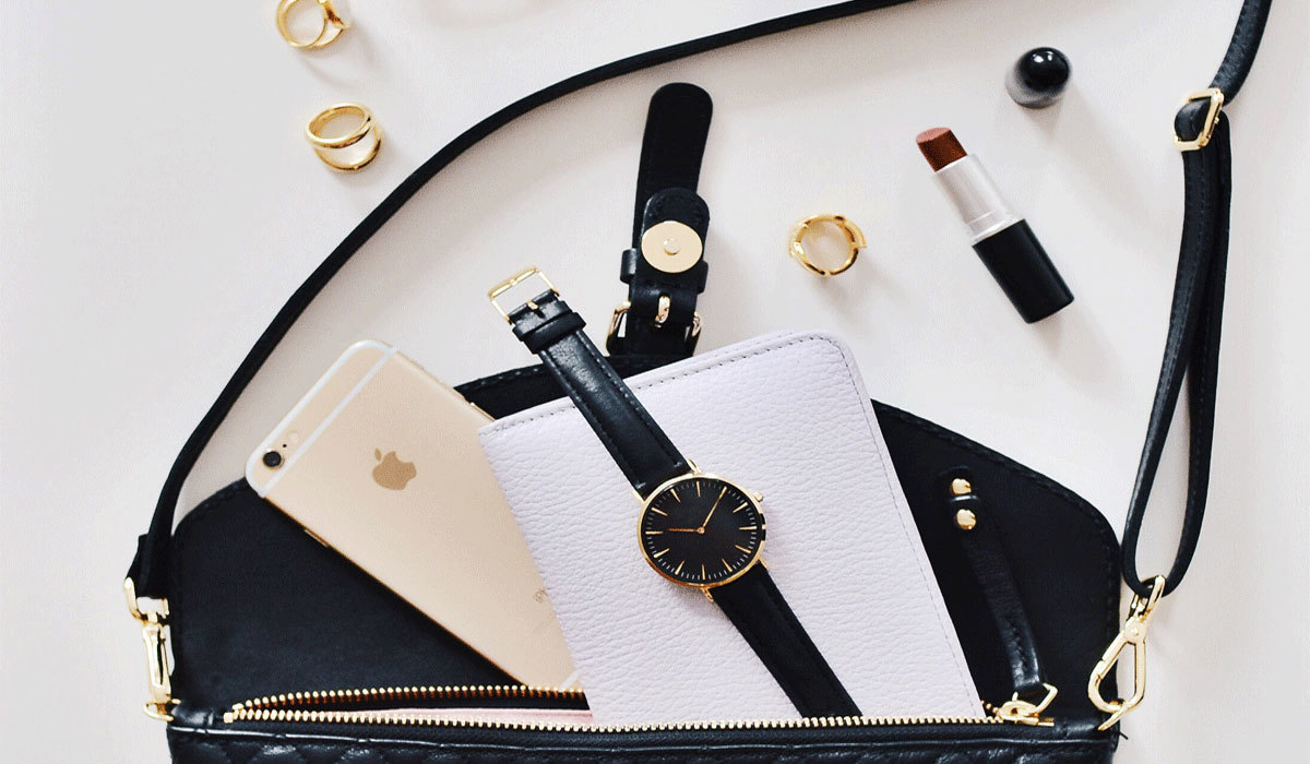 A black crossbody bag with a watch, iPhone, wallet, lipstick, and rings.