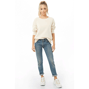 A woman wears an off-white sweatshirt, jeans, and sneakers photo