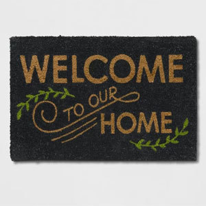Black doormat with the words welcome to our home accented with greenery photo