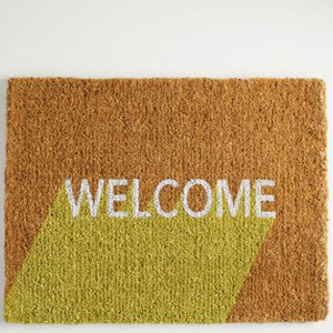 Natural colored doormat with a yellow color-block design and the words Welcome on it in white letters. photo