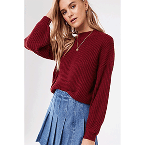A woman wears a red sweater and pleated denim skirt photo