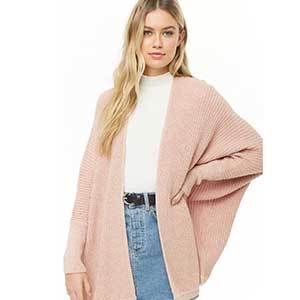 A woman wears a blush dolman-sleeve cardigan with a white tee and denim skirt photo