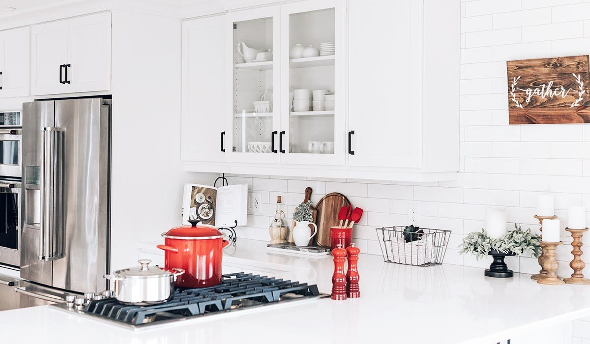 White kitchen with red accents and plant decor