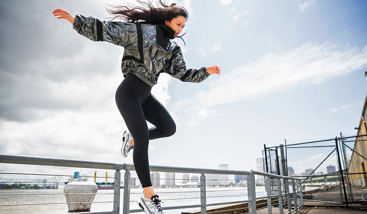 Woman jumping over a rail wearing a silver jacket and leggings by New Balance