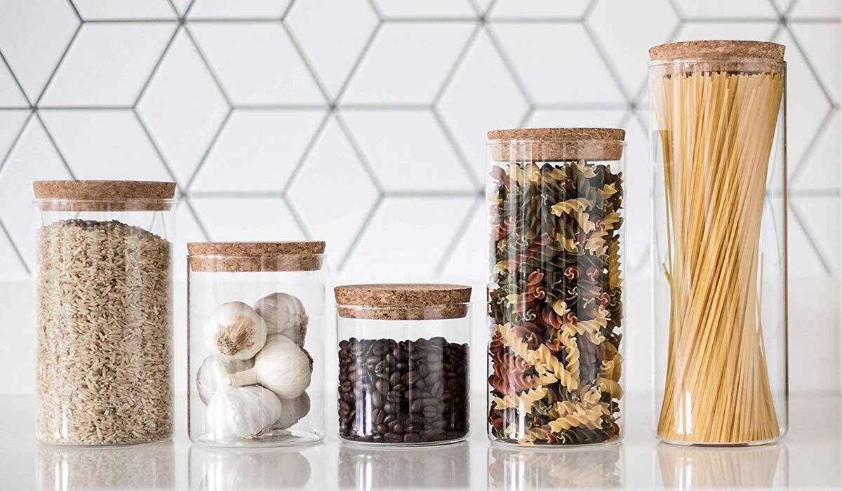 Five glass food storage canisters in various sizes from Amazon filled with dry grains, coffee beans, and garlic lined up on a white kitchen counter photo