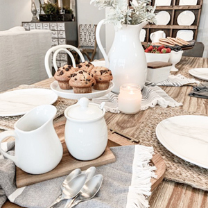 Table setting for brunch with a porcelain pitcher, fringe dish towels, and a cream and sugar set photo