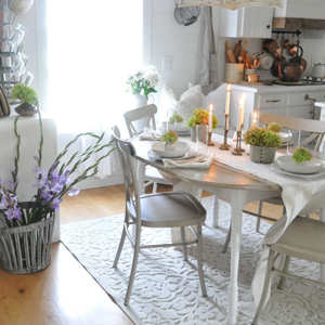Round dining table with distressed dining chairs and plates and pasta bowls photo