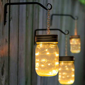 Three mason jars hanging from hooks with lights in them photo