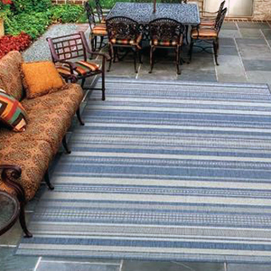 White and gray striped outdoor area rug with a patio sofa and table with chairs photo