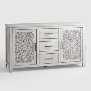 Light gray dresser from World Market with carved floral detailing on the cabinets and three drawers in the middle photo