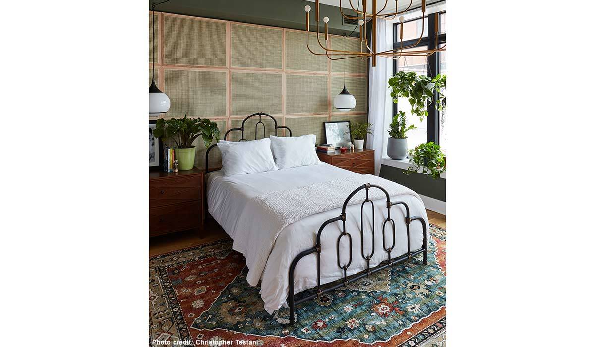 Bedroom with white sheets, metal headboard, and chandelier photo