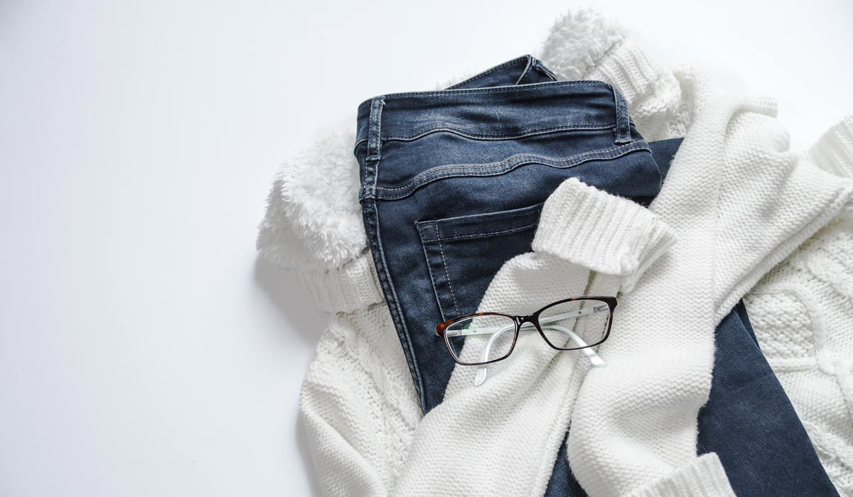 A chunky knit sweater, jeans, and glasses
