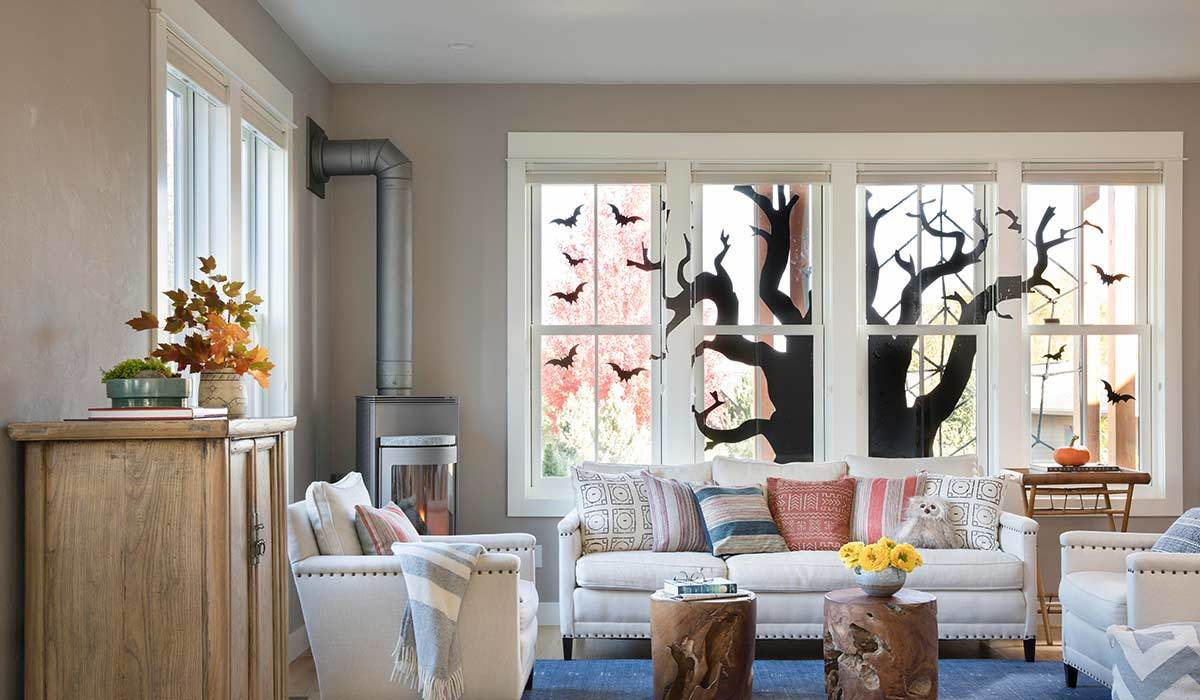 Living room with a window stencil shaped like a tree and white furniture