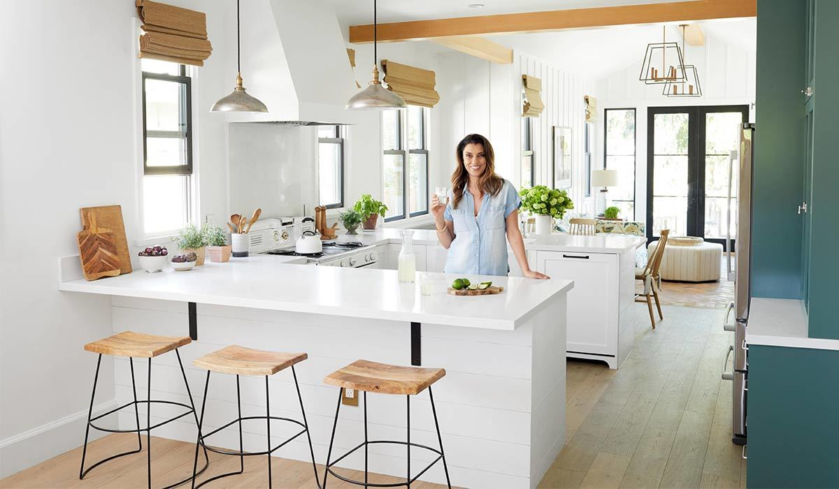 Woman standing in a white and blue kitchen with three wooden stools photo
