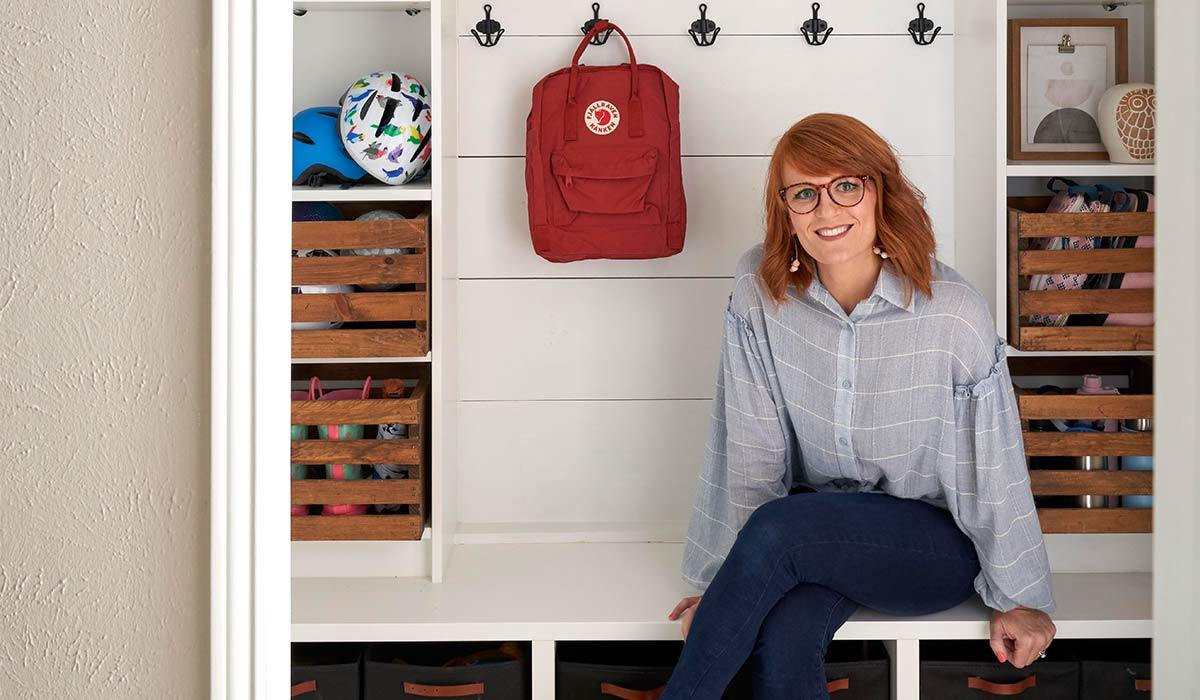 Woman sitting on a bench in a DIY mudroom photo