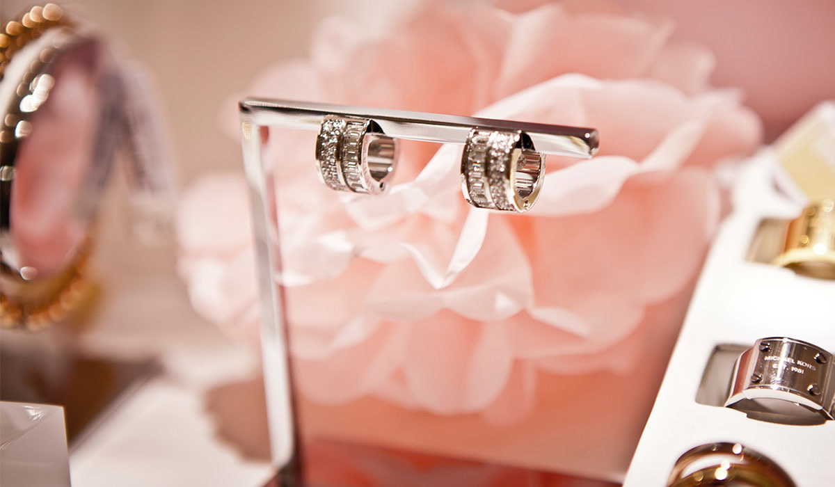 Pink flower with earrings hanging from a jewelry holder and rings in a box