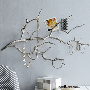 Silver branch on a wall with jewelry hanging from the limbs photo