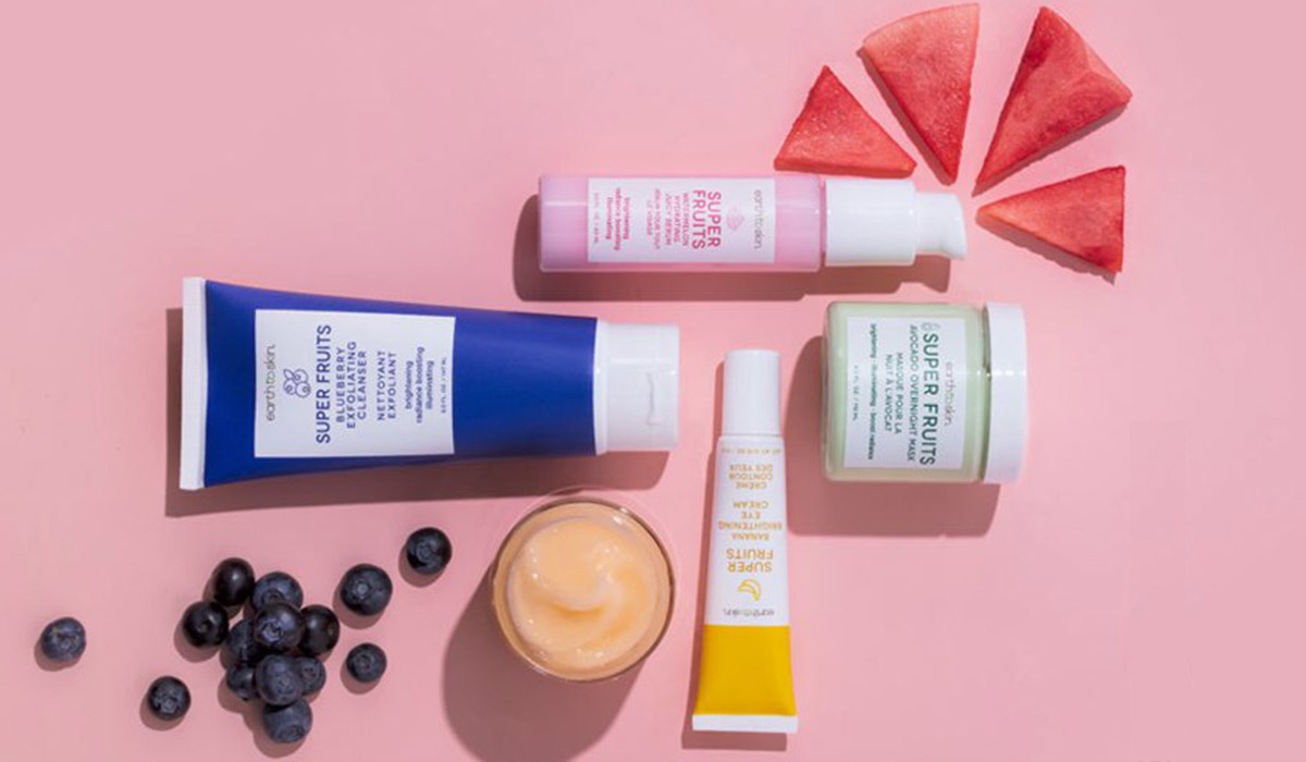 Earth to Skin products against a pink background with fruits around them photo