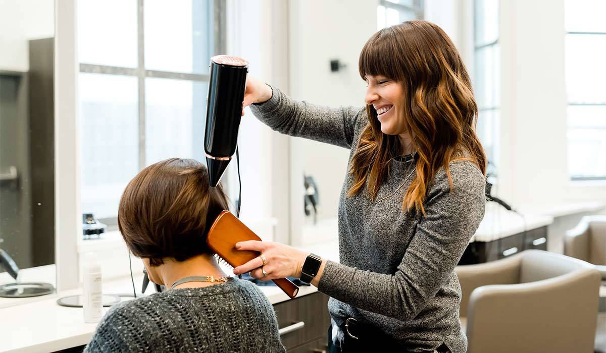 Woman getting her hair blow-dried at a salon