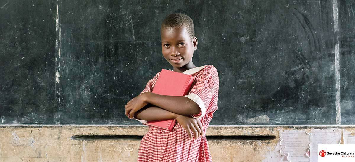 A girl holds a book in a classroom
