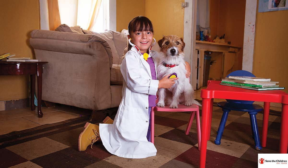 A girl plays veterinarian with a dog photo