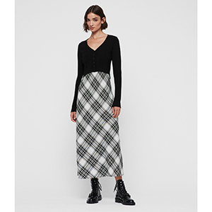 A woman wears a black top with a black and white plaid skirt photo