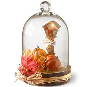 Glass centerpiece with pumpkins and a sign that reads