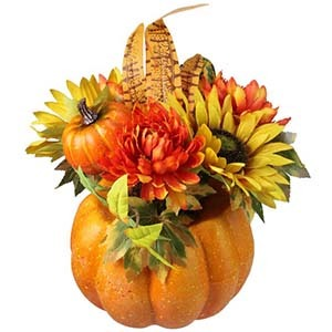 Artificial pumpkin with artificial sunflowers and feathers photo
