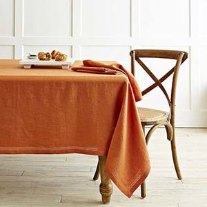 Orange tablecloth on a table with a chair photo
