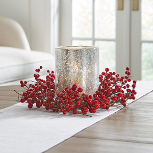 Mini red berry wreath around a candle on a dining table from Crate and Barrel photo
