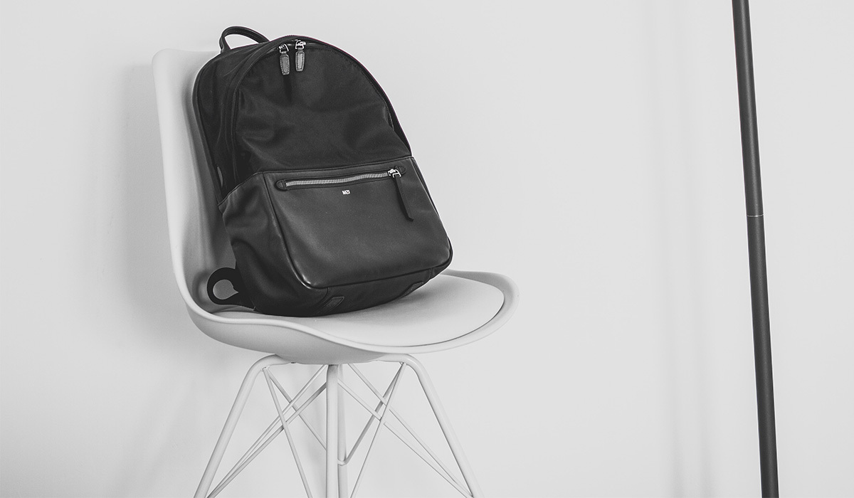 Small black backpack on a white chair next to a lamp