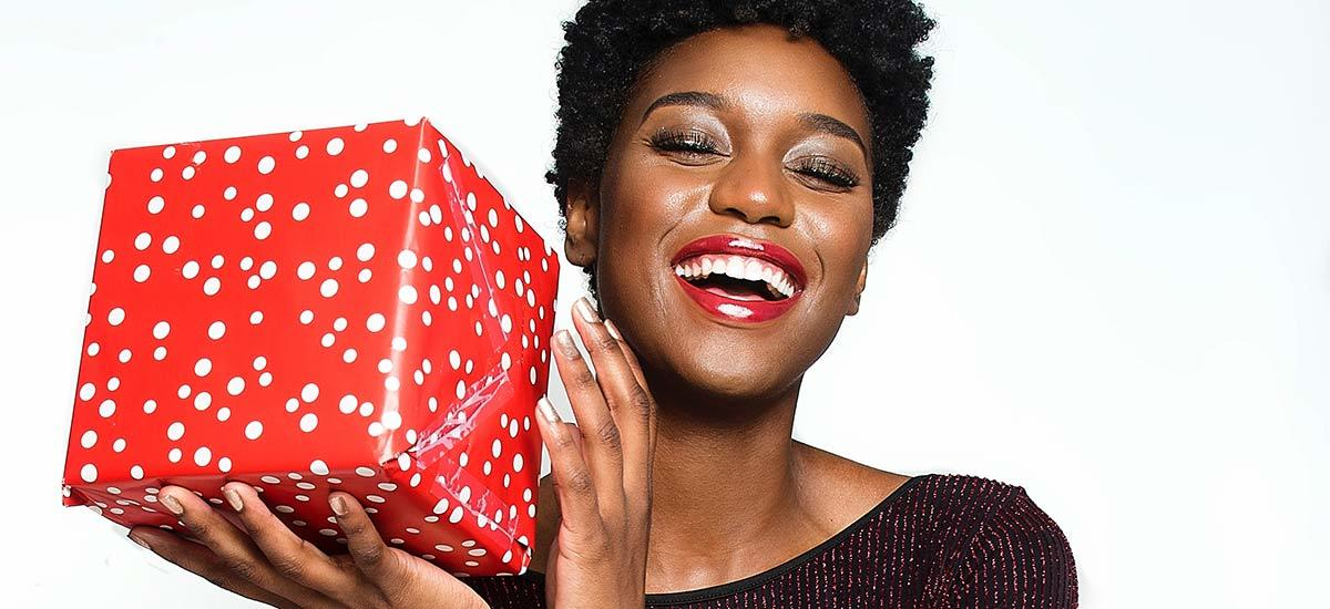 A woman wearing red lipstick smiles holding a Christmas present